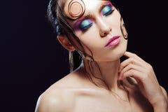 De jonge mooie meisjes heldere make-up met een natte blik glanst, donkere achtergrond Royalty-vrije Stock Foto's