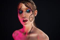 De jonge mooie meisjes heldere make-up met een natte blik glanst, donkere achtergrond Royalty-vrije Stock Afbeeldingen