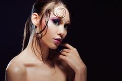 De jonge mooie meisjes heldere make-up met een natte blik glanst, donkere achtergrond Stock Foto