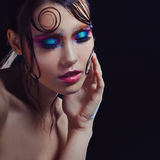 De jonge mooie meisjes heldere make-up met een natte blik glanst, donkere achtergrond Stock Afbeeldingen