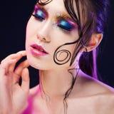 De jonge mooie meisjes heldere make-up met een natte blik glanst, donkere achtergrond Stock Fotografie