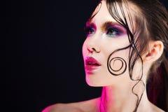 De jonge mooie meisjes heldere make-up met een natte blik glanst, donkere achtergrond Royalty-vrije Stock Fotografie