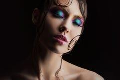 De jonge mooie meisjes heldere make-up met een natte blik glanst, donkere achtergrond, donker geheimzinnig silhouet in de schaduw Stock Foto
