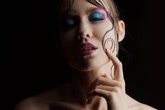 De jonge mooie meisjes heldere make-up met een natte blik glanst, donkere achtergrond, donker geheimzinnig silhouet in de schaduw Stock Afbeeldingen