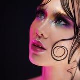 De jonge mooie meisjes heldere make-up met een natte blik glanst, donkere achtergrond, roze licht, discostijl Stock Afbeeldingen