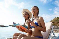 De jonge mooie meisjes in het swimwear glimlachen, doorbladeren tijdschrift bij kust Royalty-vrije Stock Foto's