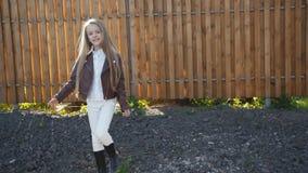 De jonge mooie meisjesgangen met stelt op manege bij camera 4K stock video