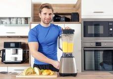 De jonge mooie mens maakt smoothy met een mixer stock afbeelding