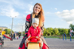 De jonge mooie moeder in een sweater speelt en berijdt op een schommeling met haar weinig babydochter in een rood jasje en hoed o Stock Fotografie