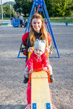 De jonge mooie moeder in een sweater speelt en berijdt op een schommeling met haar weinig babydochter in een rood jasje en hoed o Royalty-vrije Stock Foto
