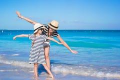 De jonge mooie moeder en haar aanbiddelijke kleine dochter hebben pret bij tropisch strand Stock Afbeelding