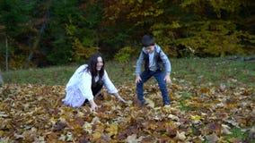 De jonge mooie moeder en haar weinig zoon hebben pret in het de herfstbos zij springen en bladeren in de lucht werpen zij stock video