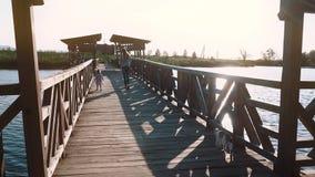 De jonge mooie moeder gaat met een kind op een houten brug tijdens zonsondergang, dichtbij het meer stock video