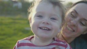 De jonge mooie moeder heeft pret met haar dochter in de lentepark stock video