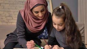De jonge mooie moeder in hijab die thuiswerk doen, weinig dochter schildert met kleurpotloden, trekt, kinderen` s kleuring stock videobeelden