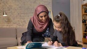 De jonge mooie moeder in hijab die thuiswerk doen, weinig dochter schildert met kleurpotloden, trekt, kinderen` s kleuring stock footage