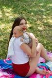 De jonge mooie moeder in rode borrels houdt haar leuke baby om na het voeden te boeren, zittend op deken in park tijdens hete de  royalty-vrije stock afbeeldingen