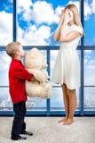 De jonge mooie moeder sloot zijn ogen met zijn handen, geeft de zoon mamma een gift, een verrassing, een grote witte Teddybeer De Stock Foto