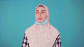 De jonge mooie Moslimvrouw in medisch masker, stijgt masker op die en camera glimlachen bekijken stock videobeelden