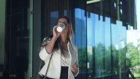 De jonge mooie onderneemster heeft koffiepauze die zich dichtbij de bedrijfbouw bevinden stock video
