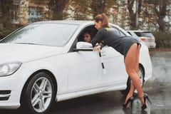 De jonge mooie politievrouw houdt auto voor het controleren van bestuurder tegen Stock Afbeeldingen