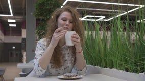 De jonge mooie roodharige vrouw zit in een koffie en eet heemst van koffie stock footage