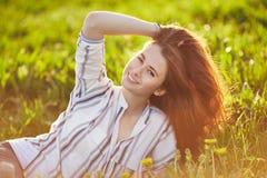 De jonge mooie roodharigevrouw zit op een groene weide, bekijkend camera stock foto