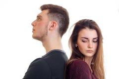 De jonge mooie ruggen van de paartribune aan elkaar en het meisje draaiden haar hoofd op witte achtergrond Royalty-vrije Stock Foto