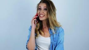 De jonge mooie sexy blondevrouw beantwoordt de vraag op haar smartphone en kijkt verbaasd terwijl het hebben van gesprek op geïso stock videobeelden