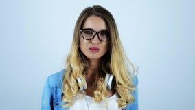 De jonge mooie sexy kauwgom van de blondevrouw met hoofdtelefoons op haar hals die haar oogglazen op geïsoleerde witte achtergron stock videobeelden