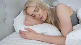 De jonge mooie slaap van de blondevrouw in haar slaapkamer stock video