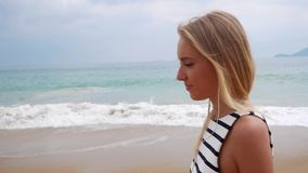 De jonge mooie slanke vrouw met lang blondehaar in zwart-witte kleding met hoofdtelefoons en luistert aan muziek het lopen stock videobeelden
