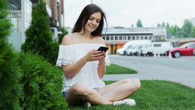 De jonge mooie smartphone van het vrouwengebruik terwijl het zitten op het gras dichtbij het hotel stock videobeelden