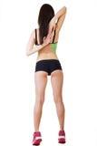 De jonge mooie sportieve vrouw die sportenborrels en bovenkant dragen bevindt zich met zijn rug Stock Foto's