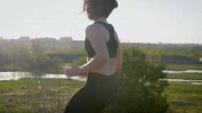 De jonge mooie sportvrouw is bezig geweest met geschiktheid in aard Het meisje voert oefeningen buiten de stad uit steadicam scho stock video