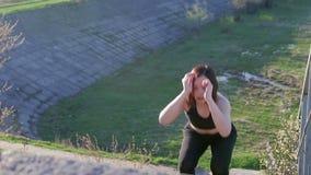 De jonge mooie sportvrouw is bezig geweest met geschiktheid in aard Het meisje voert oefeningen buiten de stad uit steadicam scho stock footage