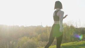 De jonge mooie sportvrouw is bezig geweest met geschiktheid in aard Het meisje voert oefeningen buiten de stad uit steadicam scho stock videobeelden