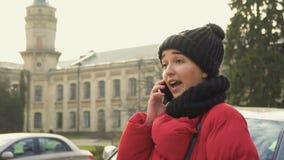De jonge mooie student heeft gesprek in openlucht op telefoon stock video