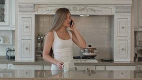 De jonge mooie telefoon van de vrouwen sprekende cel, drank stock videobeelden