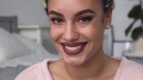 De jonge mooie vrouw bekijkt omhoog camera en het glimlachen stock footage