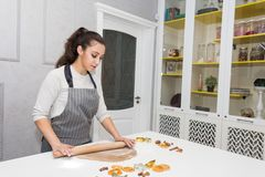 De jonge mooie vrouw bereidt het deeg voor en bakt peperkoek en koekjes in de keuken Vrolijke Kerstmis en Gelukkige Nieuw stock afbeelding