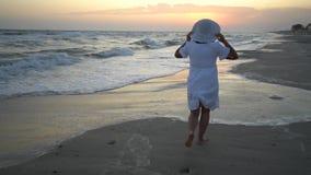 De jonge mooie vrouw bevindt zich door het overzees bij zonsondergang In een witte kleding en een witte hoed stock footage