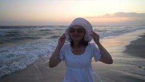 De jonge mooie vrouw bevindt zich door het overzees bij zonsondergang In een witte kleding en een witte hoed Zij bekijkt de camer stock videobeelden