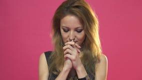De jonge mooie vrouw bidt op roze achtergrond stock videobeelden
