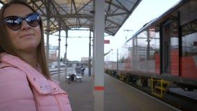 De jonge mooie vrouw bij het station gaat naar de trein Met glazen, lang haar, roze jasje stock footage