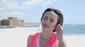 De jonge mooie vrouw brengt oortelefoons aan alvorens op een strand op te leiden De sterke golven raken de kust stock videobeelden