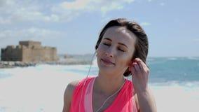 De jonge mooie vrouw brengt oortelefoons aan alvorens op een strand op te leiden De sterke golven raken de kust Langzame motie stock videobeelden