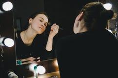 De jonge mooie vrouw die haar toepassen maakt omhoog gezicht met borstel, bekijkend in een spiegel, zittend op stoel kleedkamer m Royalty-vrije Stock Foto's