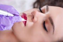 De jonge mooie vrouw die permanent hebben maakt omhoog of tatoegering op haar lippen royalty-vrije stock afbeeldingen