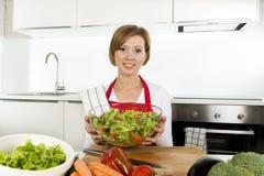 De jonge mooie vrouw die van de huiskok bij moderne keuken het plantaardige saladekom gelukkig glimlachen voorbereiden Royalty-vrije Stock Afbeeldingen